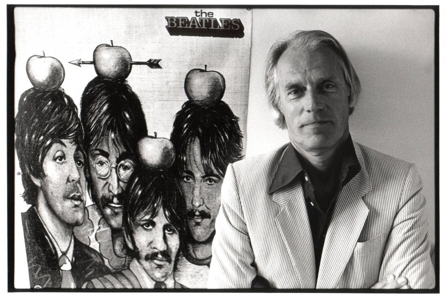 Older George Martin stands in front of a drawing of The Beatles.