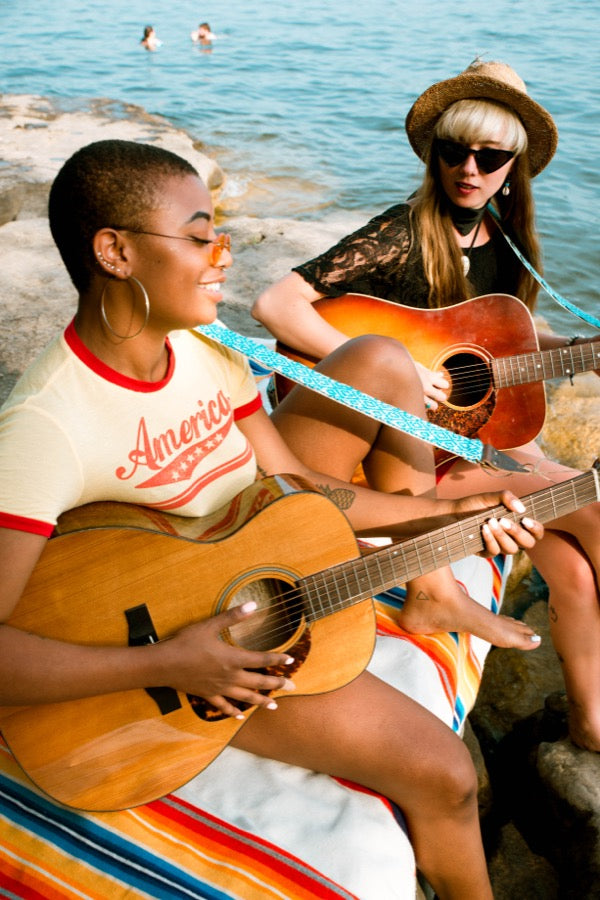 Girls with handwoven Original Fuzz guitar straps sitting by the lake in Nashville.