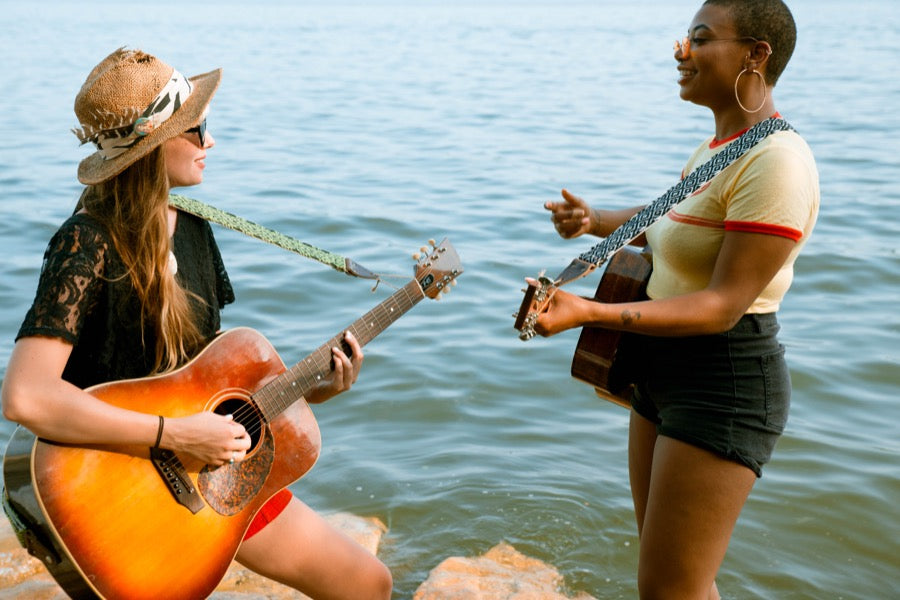 Two girls with handwoven Original Fuzz guitar straps standing by the lake in Nashville.