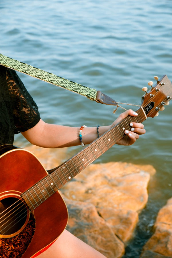 Girl with handwoven Original Fuzz guitar straps sitting by the lake in Nashville.