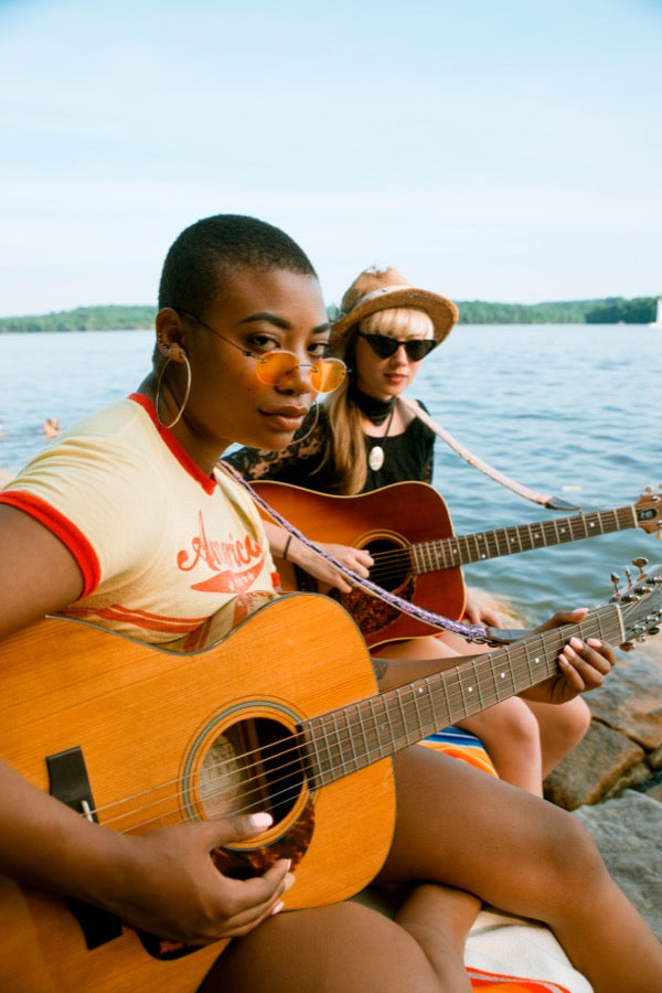 Two girls with handwoven Original Fuzz guitar straps sitting by the lake in Nashville.
