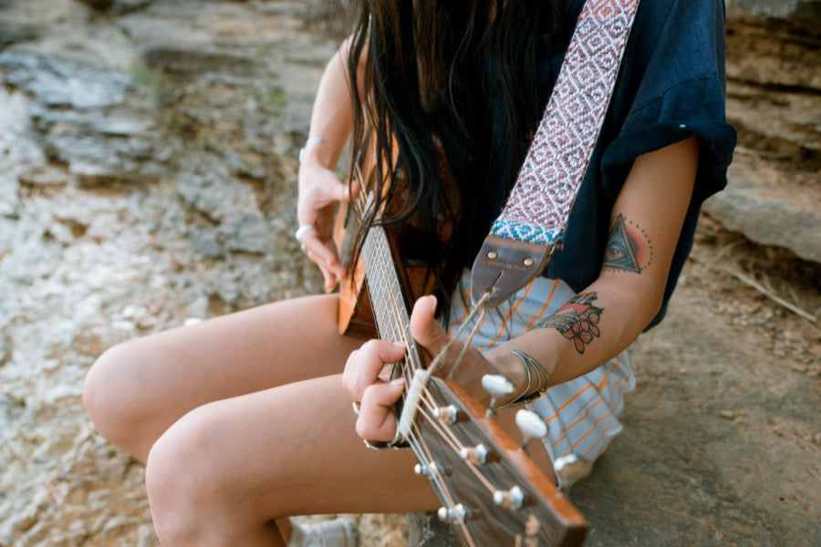 Girl with handwoven Original Fuzz guitar strap sitting by the lake in Nashville.