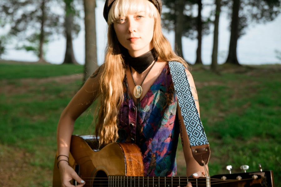 Girl with handwoven Original Fuzz guitar strap standing by the lake in Nashville.