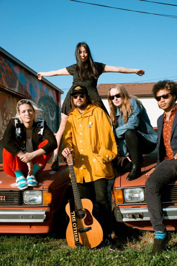 King Tuff and his band hanging out in Nashville with old cars behind the Basement East.