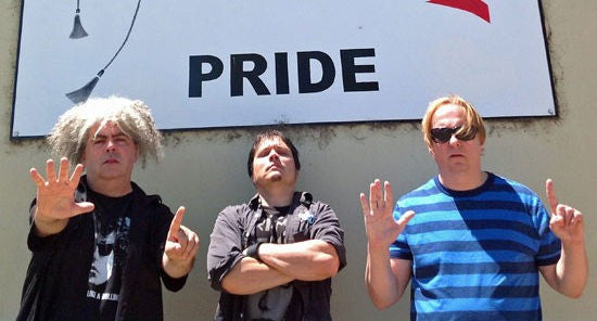 The Melvins stand in front of a sign that says Pride