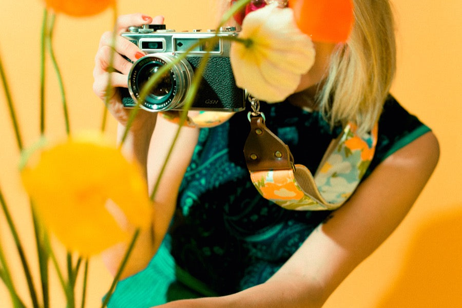 Girl holding vintage camera strap with poppies in mod photoshoot.