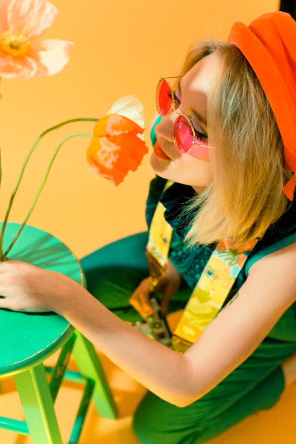 Girl smelling poppies in mod photoshoot.
