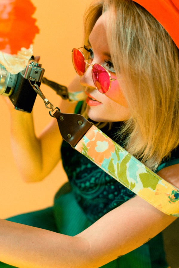 Girl taking photos of popping wearing vintage-style camera strap by Original Fuzz.
