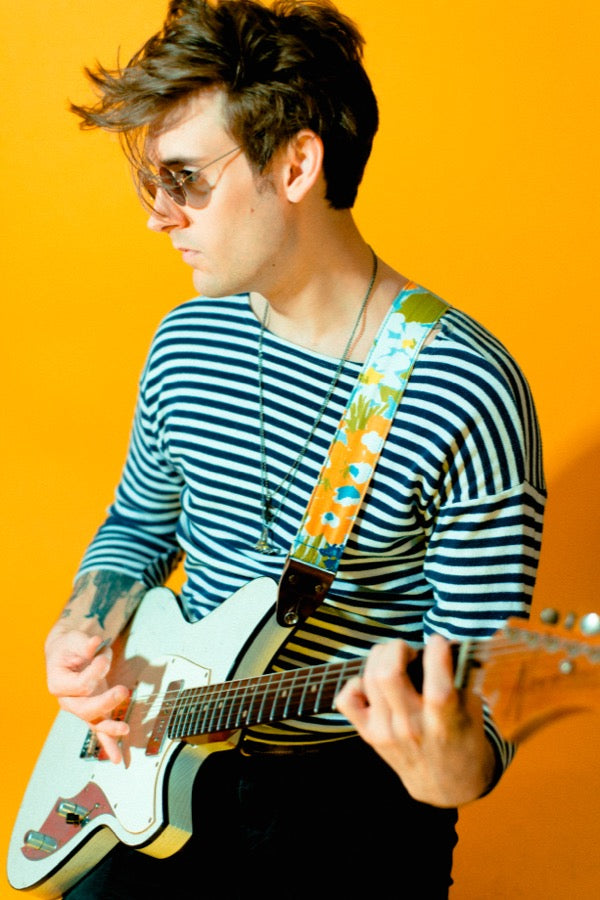 Guy wearing vintage-style guitar strap in mod photoshoot.