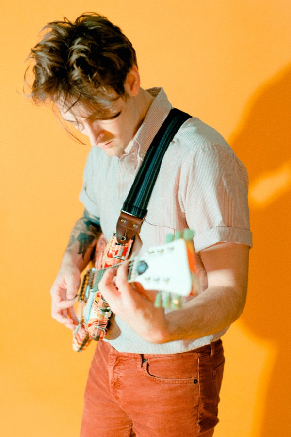 Guy wearing vintage-style guitar strap in a mod photoshoot.
