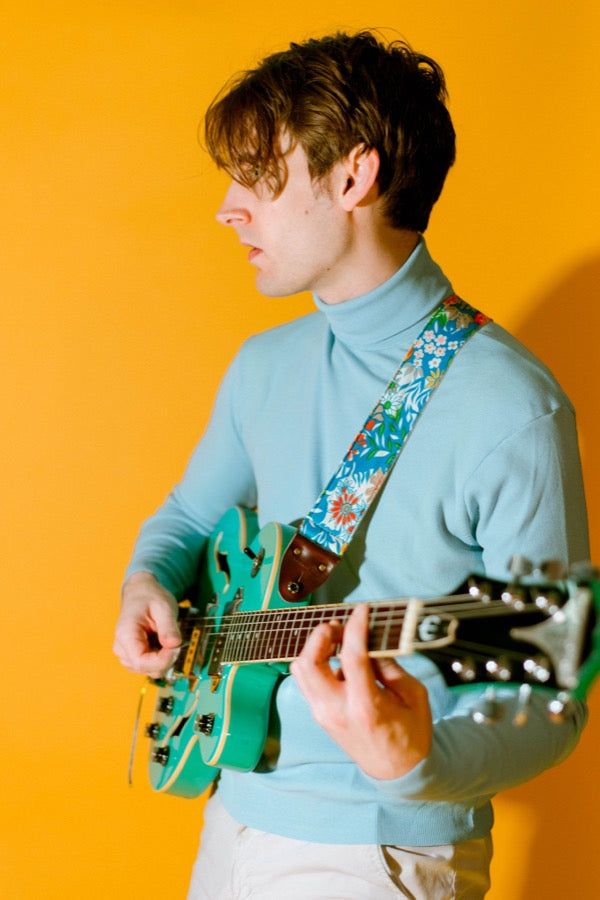 Guy wearing floral vintage-style guitar strap and blue turtleneck in mod photoshoot.