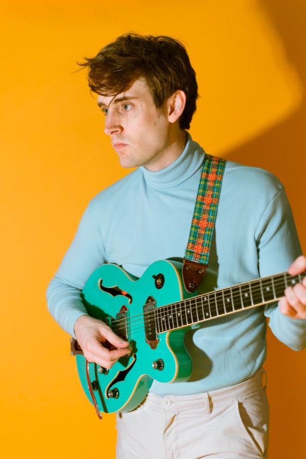 Guy wearing vintage plaid guitar strap in mod photoshoot.