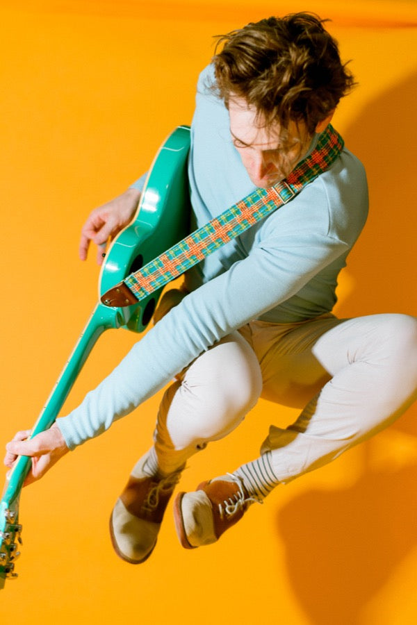 Guy jumping with vintage plaid guitar strap and teal guitar in mod photoshoot.