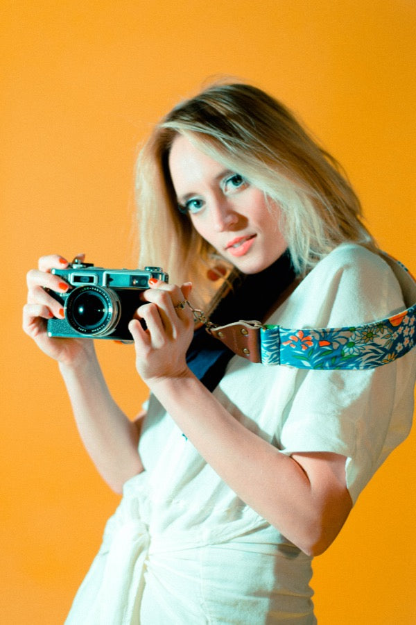 Girl with vintage blue floral camera strap in mod photoshoot.