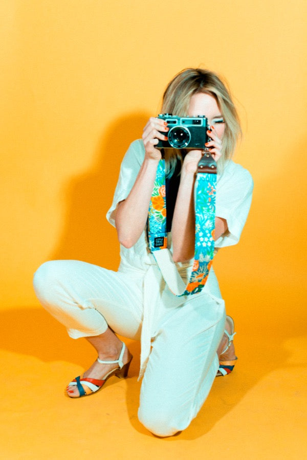 Girl posing with blue floral vintage camera strap in mod photoshoot.