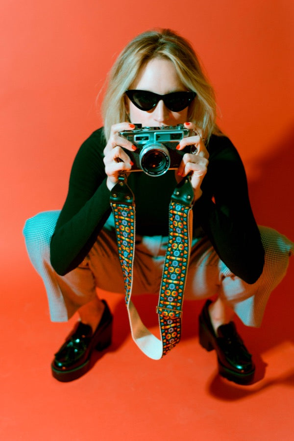 Girl posing with vintage camera strap in mod photoshoot.