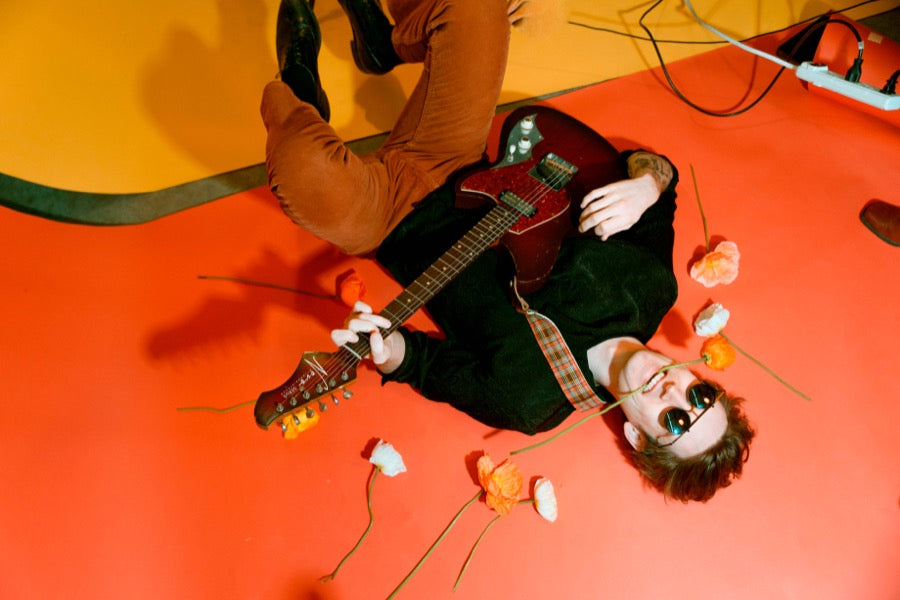 Guy lying on the floor wearing vintage guitar strap in mod photoshoot.
