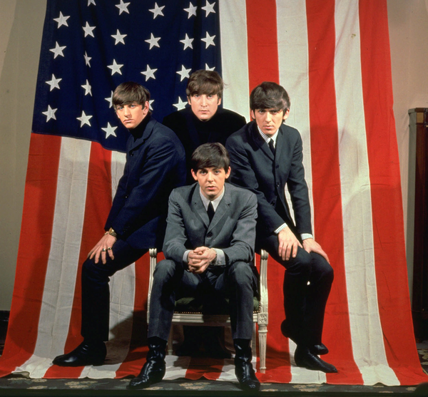 The Beatles pose in front of an American flag in a promotional photo for their 1964 trip to USA