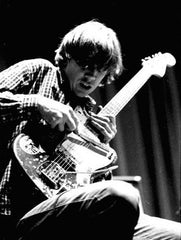 Thurston Moore of Sonic Youth plays guitar with a drum stick.