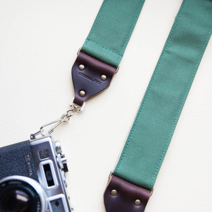Green cotton canvas vintage-style camera strap with antique brass hardware and vintage Yashica camera made by Original Fuzz.