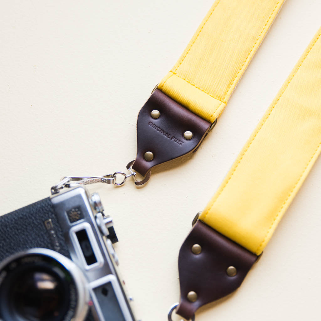 Yellow cotton canvas vintage-style camera strap with antique brass hardware made by Original Fuzz in Nashville, TN with Yashica film camera.