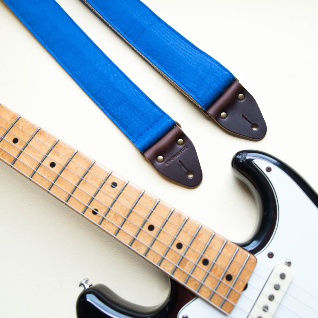 Blue vintage-style cotton canvas guitar strap made by Original Fuzz in Nashville with a Fender Jazzmaster.