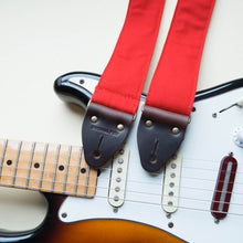 Red cotton canvas vintage-style guitar strap with antique brass hardware made by Original Fuzz in Nashville with a Fender Jazzmaster.