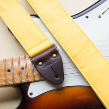 Yellow cotton canvas vintage-style guitar strap with antique brass hardware made by Original Fuzz in Nashville, TN with a Fender Jazzmaster.