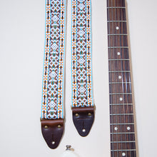 Detail of the vintage guitar strap in Merrimon Ave next to the fretboard of an electric guitar