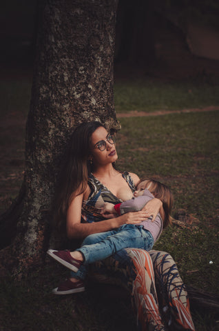 Person against a tree breastfeeding child, for The Core blog
