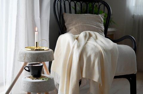 Chair with cosy blanket, candlelight and coffee cup