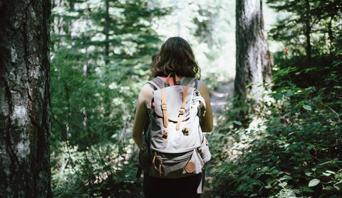 Girl hiking in the woods with backpack on