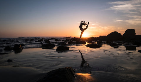 Silhouette of girl doing yoga on rocks in water in front of sunset