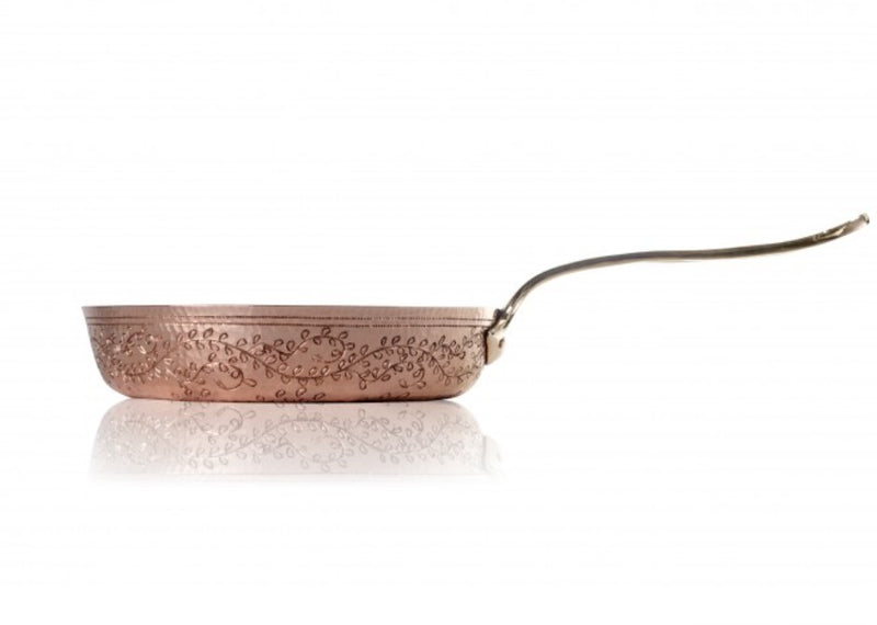 "A fine copper fry pan that harkens back to Roman elegance.  The classic look of the 9-inch ""Leaves"" Copper Fry Pan adds an elevated charm to your kitchen. Winding leaf designs cover the gleaming exterior of this fry pan. Made entirely from hand hammered copper, this copper cookware piece features a double layer of tin lining. Applied by hand, the tin layers provide an even protective coating that keeps your fry pan from wearing down."