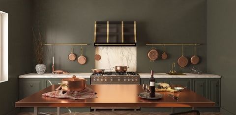 a beautiful kitchen with a copper table, a custom brass range hood, copper cookware and pots racks