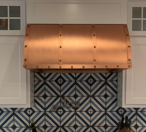 Winston the custom copper range hood with straps and rivets, barrel shape by Amoretti Brothers