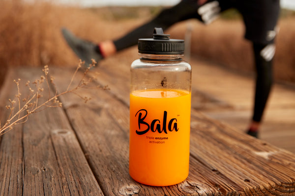 Bala bottle on a wooden bench with man stretching leg on the bench in the background.