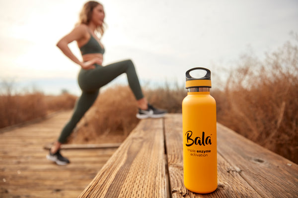 Bala bottle on a wooden bench with woman stretching legs in the background. Woman is wearing a sage green sports bra and leggings with black shoes.