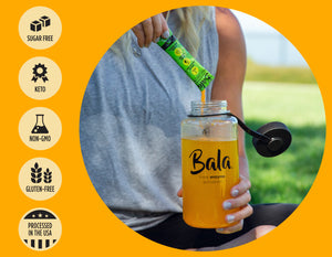 Woman pouring Bala Lime Flavor stick pack into a Bala reusable plastic bottle. Buttons on the left read from top to bottom: Sugar free, Keto, Non-GMO, Gluten-Free, and Processed in the USA.