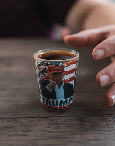 Trump Shot Glass - Trump Shot Glass.  Casual Trump pictured in a red MAGA hat, pointing, American flag design in the background.  One ounce.