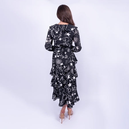 back view of the BIBA constellation print midi dress with skirt ruffles and long sleeves made in a floaty fabric, available to rent from LENDLAB