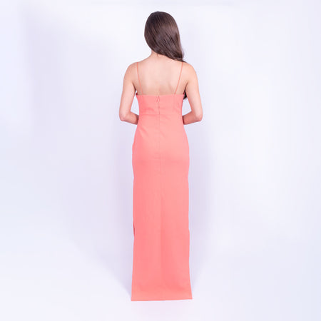 Showing the back of the Likely brand coral floor length maxi dress with spaghetti straps and side leg split available to rent from LENDLAB