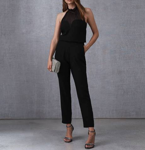 Woman wearing a black halter neck jumpsuit with one hand in pocket and the other hand holding a silver clutch bag