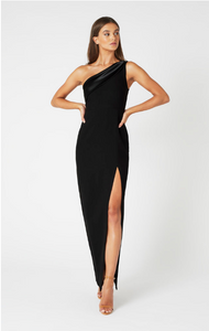 model standing with hands on her hips and one leg forward wearing one shoulder black maxi dress with leg slit