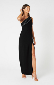 side shot of a model wearing a one shoulder black maxi dress with a leg slit