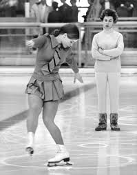 woman in background with arms crossed, watching a young woman figure skate