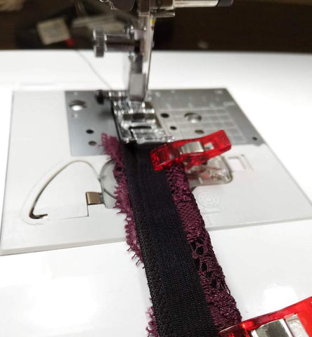 lace bra strap being sewn on machine