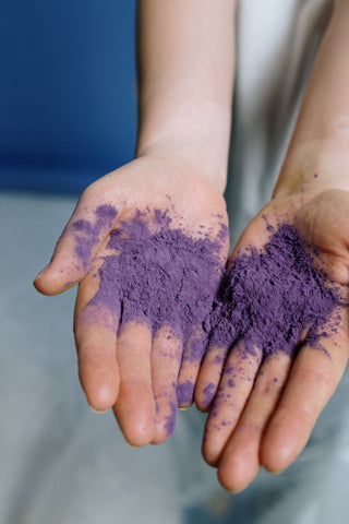 Two hands with purple colour on them