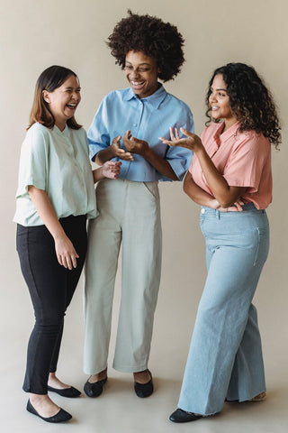 Group of women in office attire laughing together
