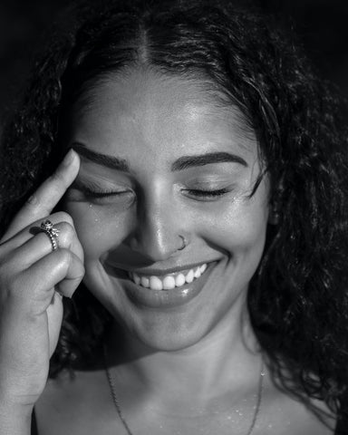 A smiling woman with her finger on her forehead